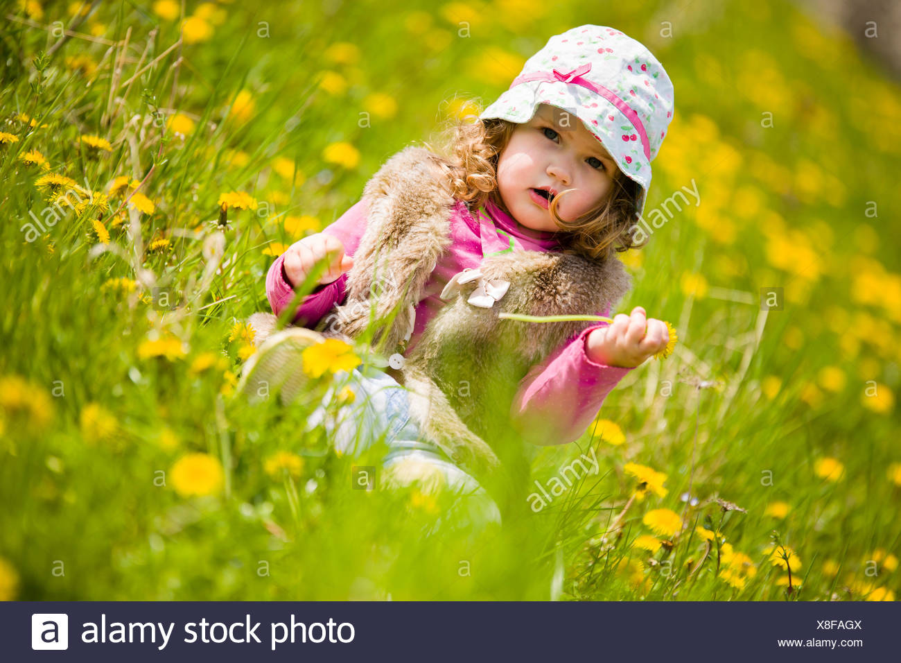 cute baby girl with sun cap on vivid flower meadow full of yellow