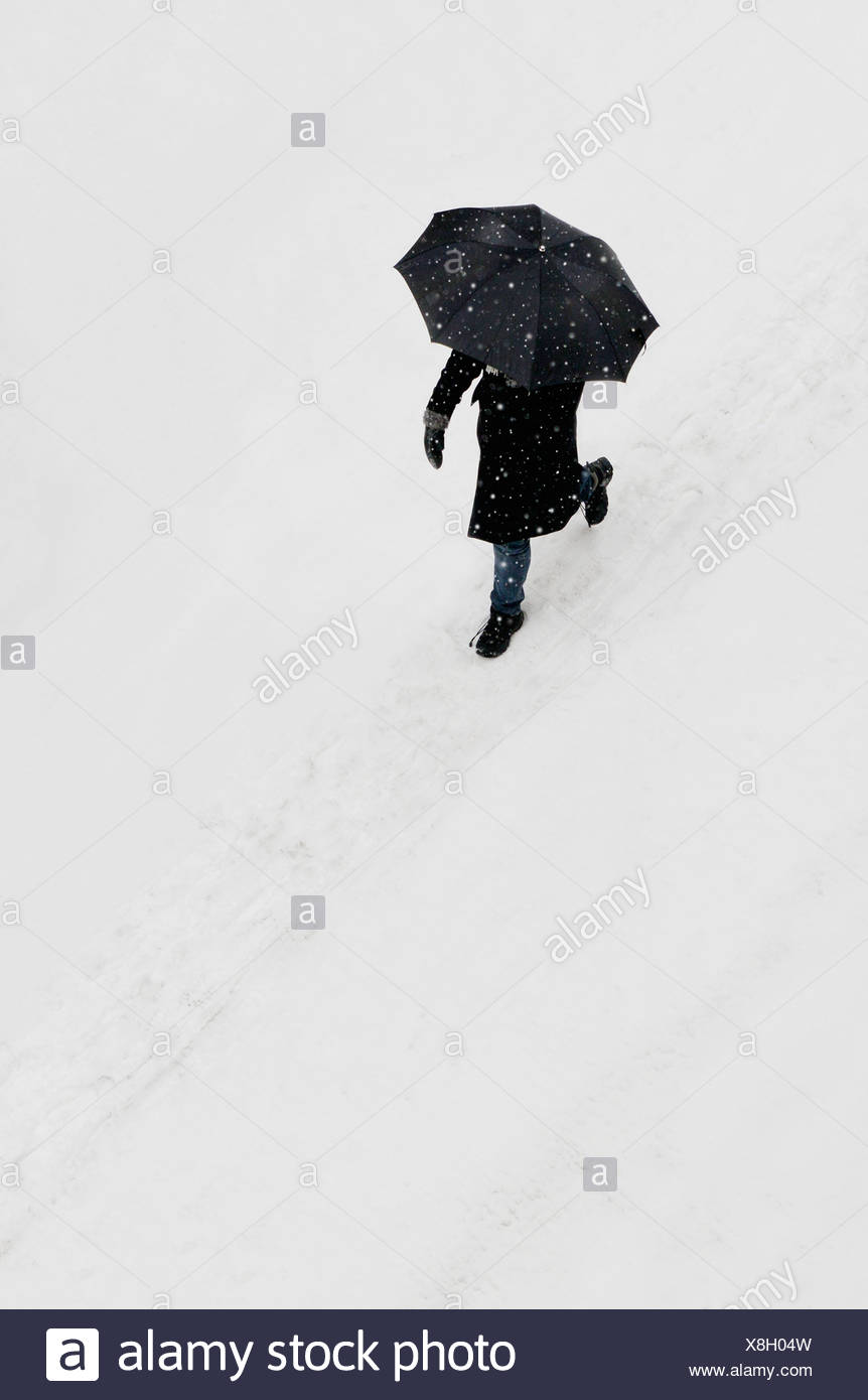 High Angle View Of Woman With Umbrella Walking In Snow Stock Photo