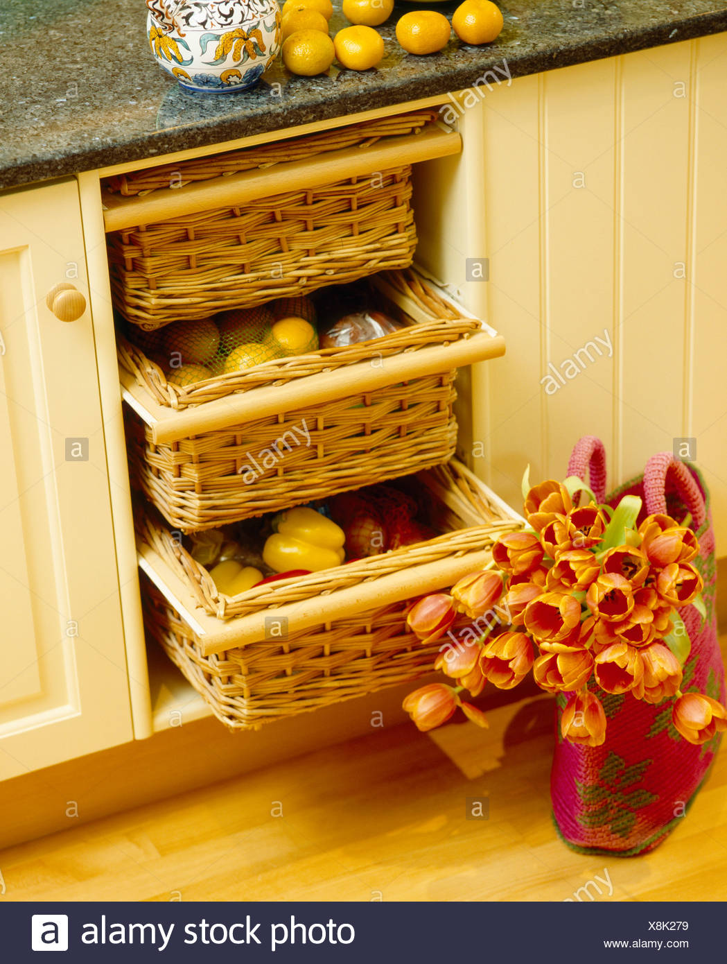 Close Up Of Orange Tulips In Basket On Floor Beside Storage Baskets In  Fitted Kitchen Unit
