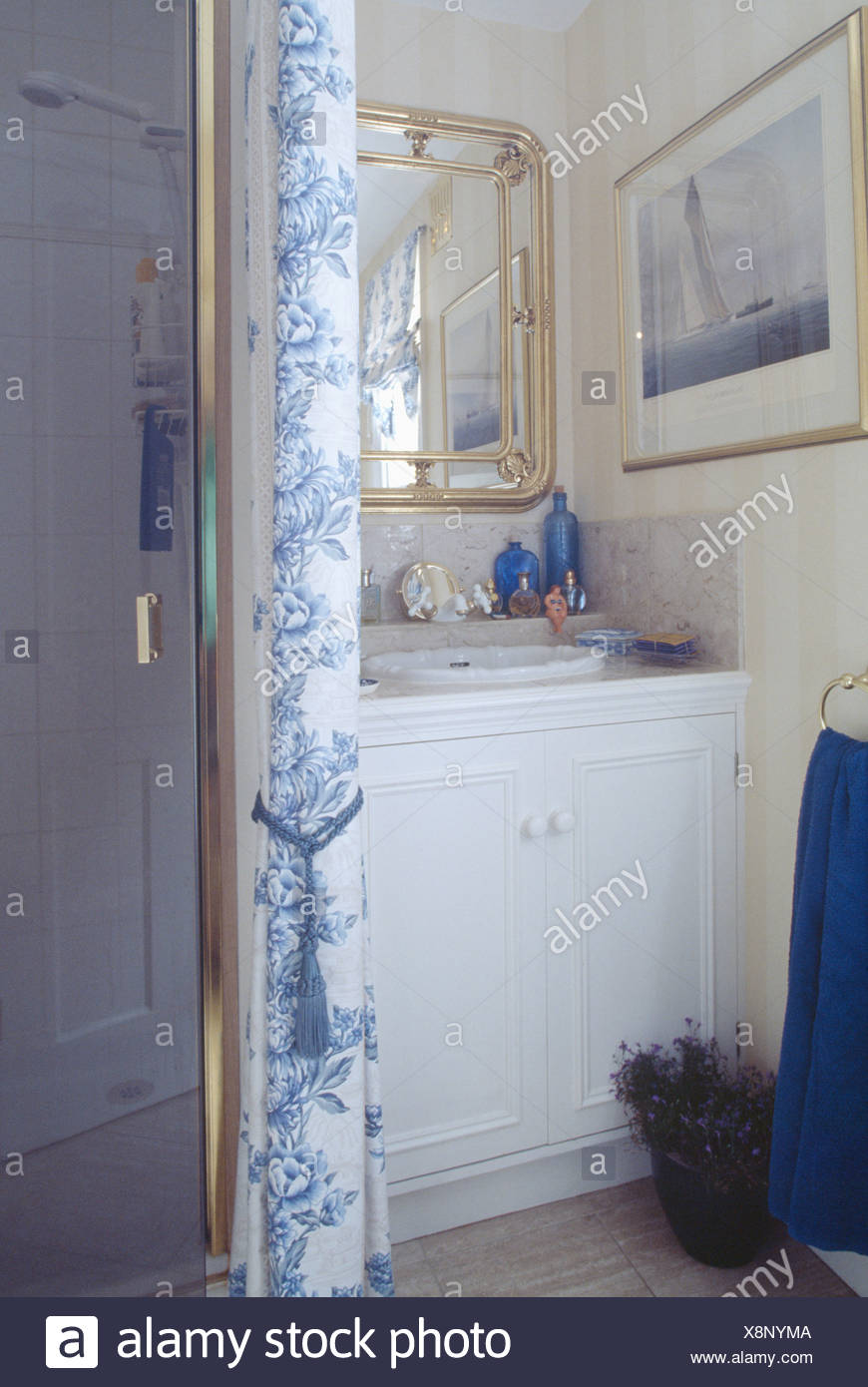 Blue and white floral curtain beside glass shower door in ...