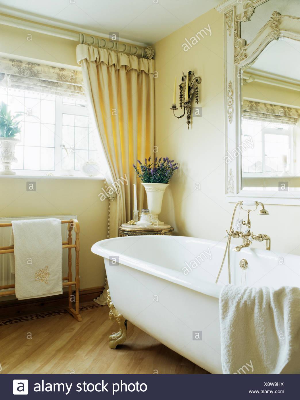Roll-top bath in cream bathroom with cream curtains on window above ...