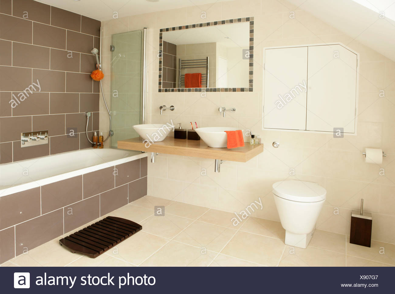 Tiled-framed mirror above white bowl basins on wooden vanity shelf ...