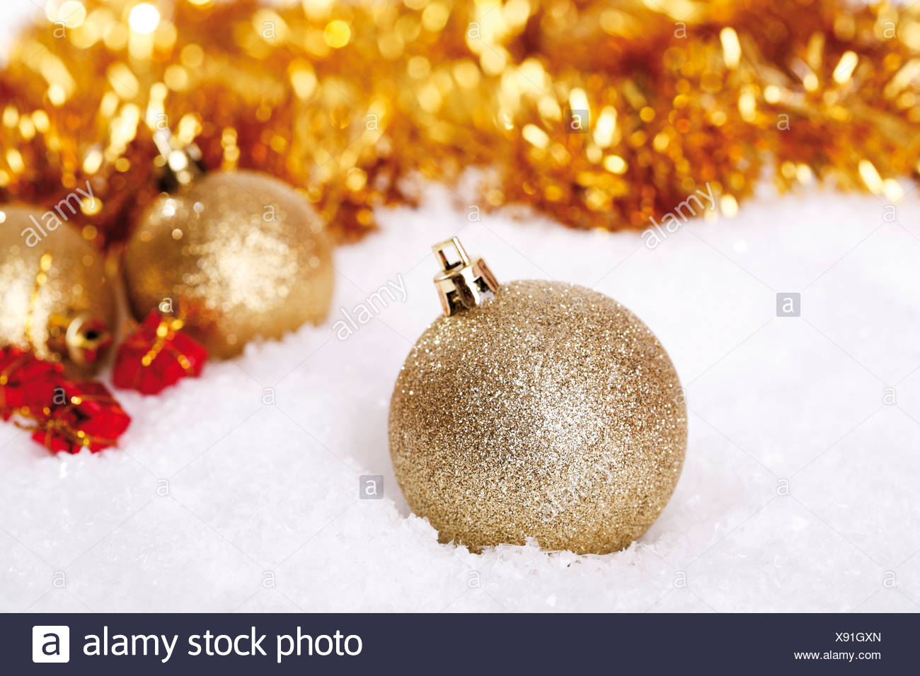gold glitter christmas tree balls on snow with christmas decorations