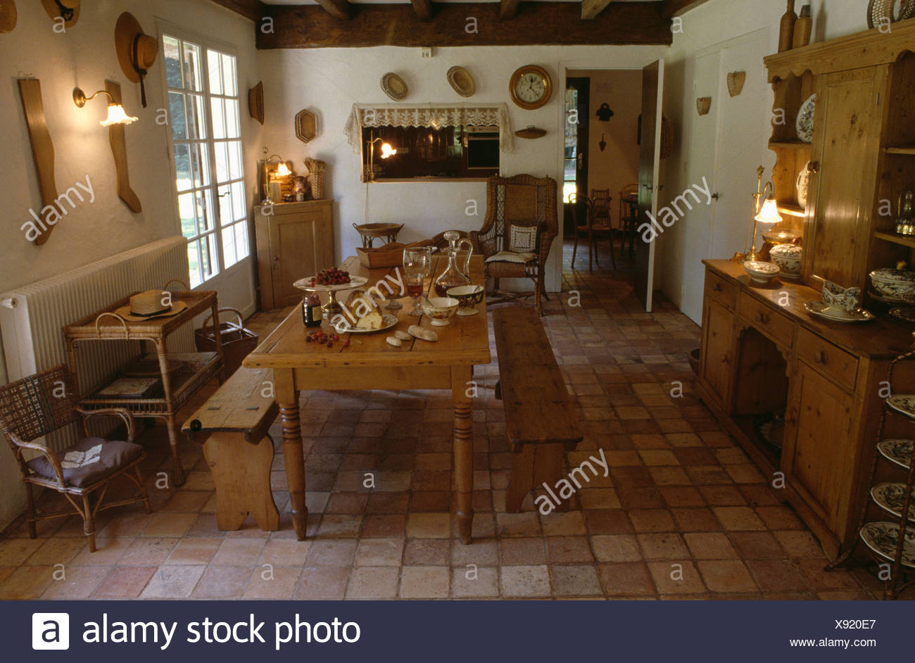 Wooden Benches And Old Pine Table On Terracotta Tiled Floor In Traditional French  Country Dining Room With Glass Wall Lights