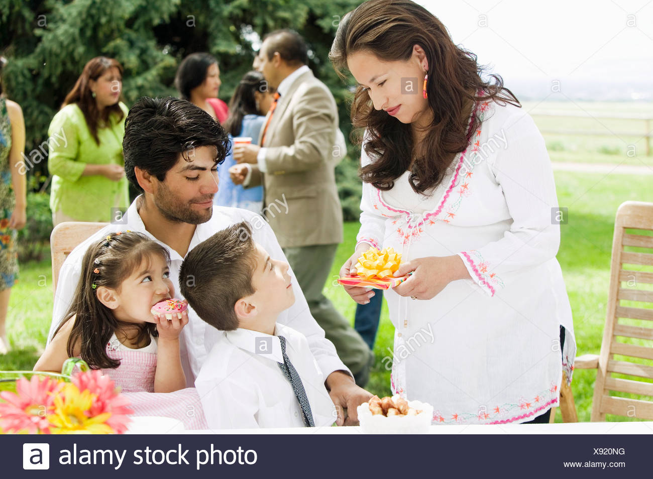 Hispanic Mother Handing Birthday Gift To Son