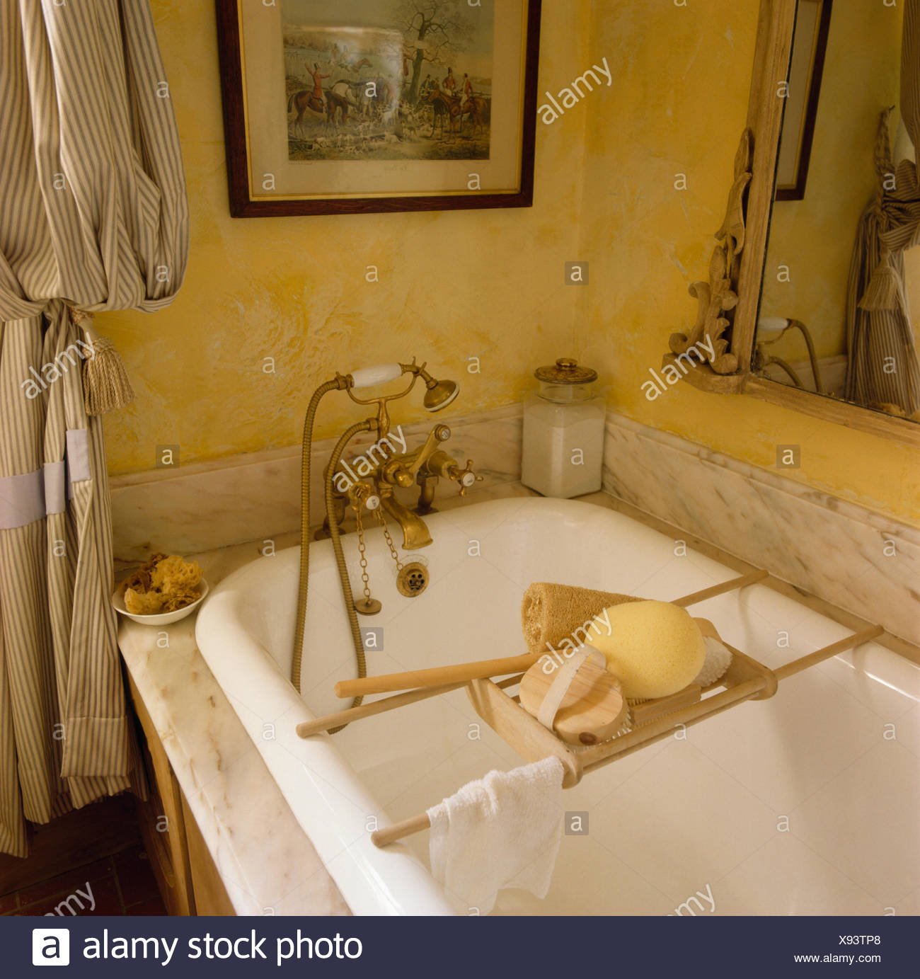 Wooden bath rack and brass shower taps on bath tub with marble ...
