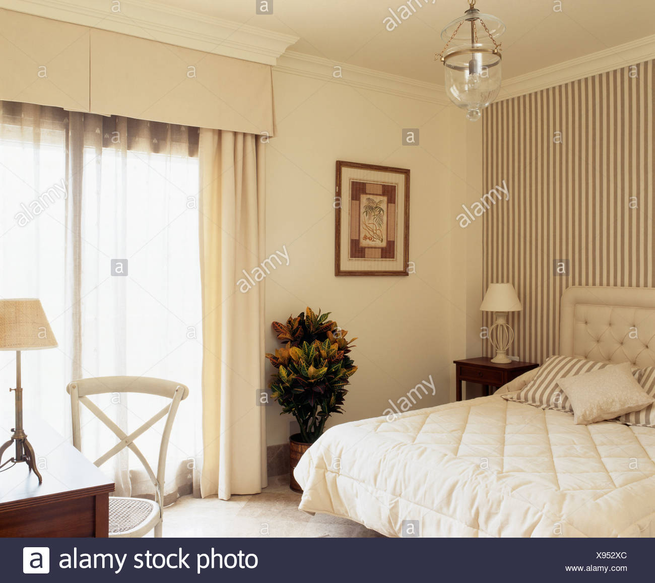 Striped Wallpaper Behind Bed With Cream Quilt In Spanish Bedroom