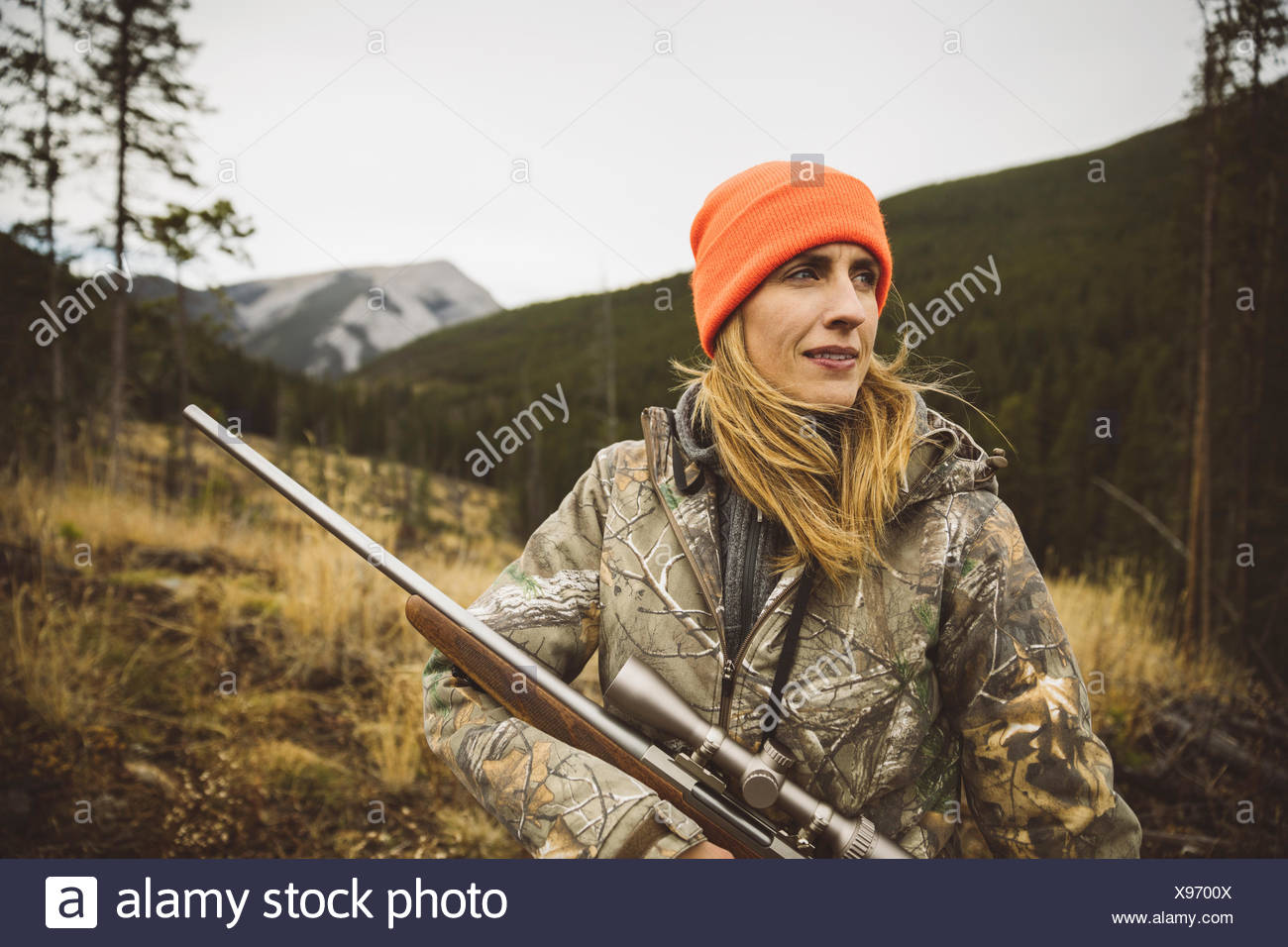 Portrait female hunter in camouflage and orange beanie holding hunting  rifle in field b3b9bc37bfd