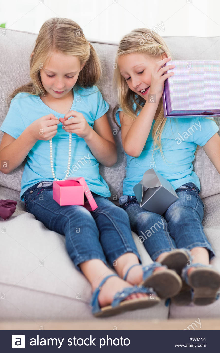 Twins Unwrapping Birthday Gift Sitting On A Couch