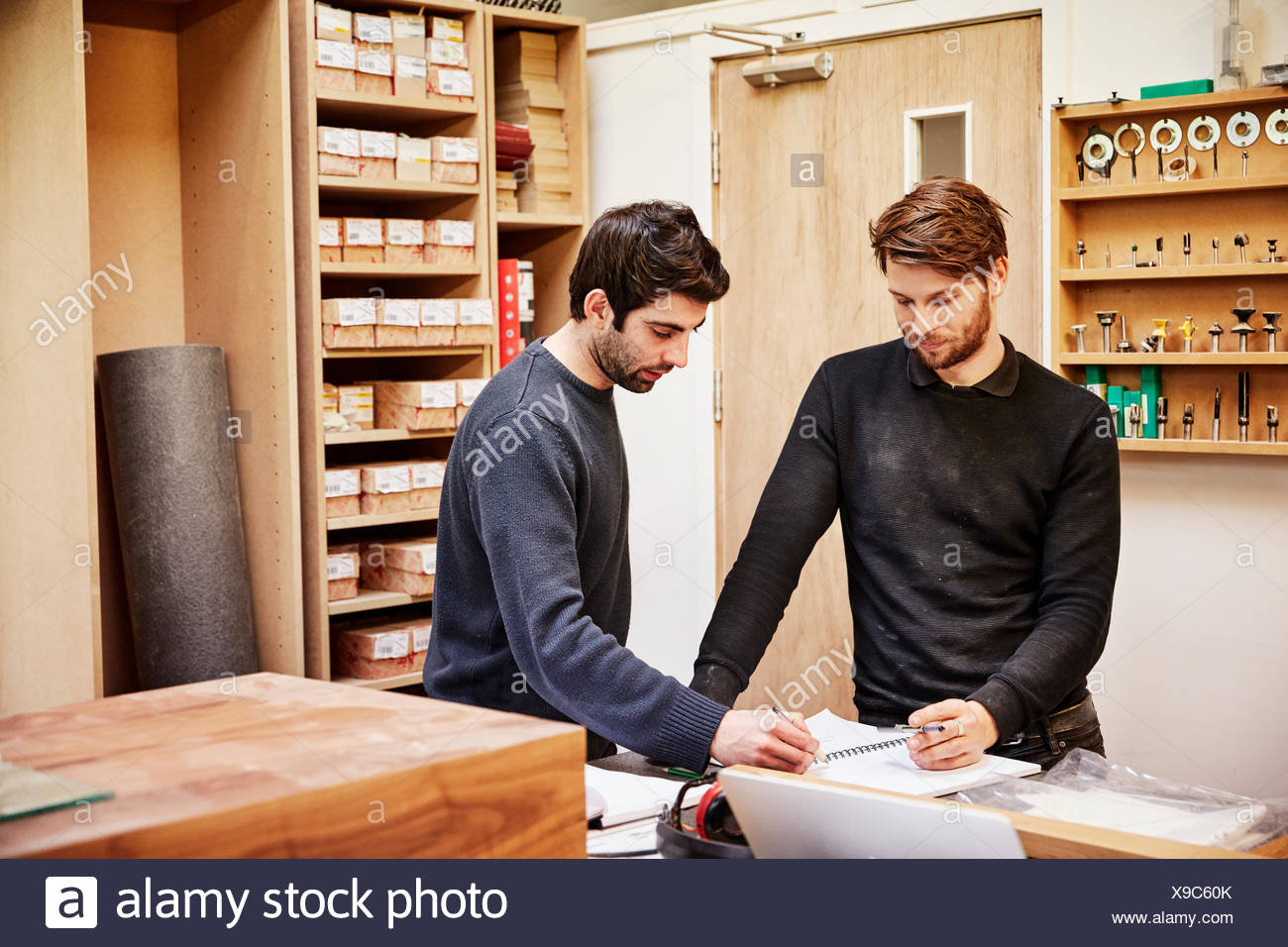 a furniture workshop two people discussing a design referring to