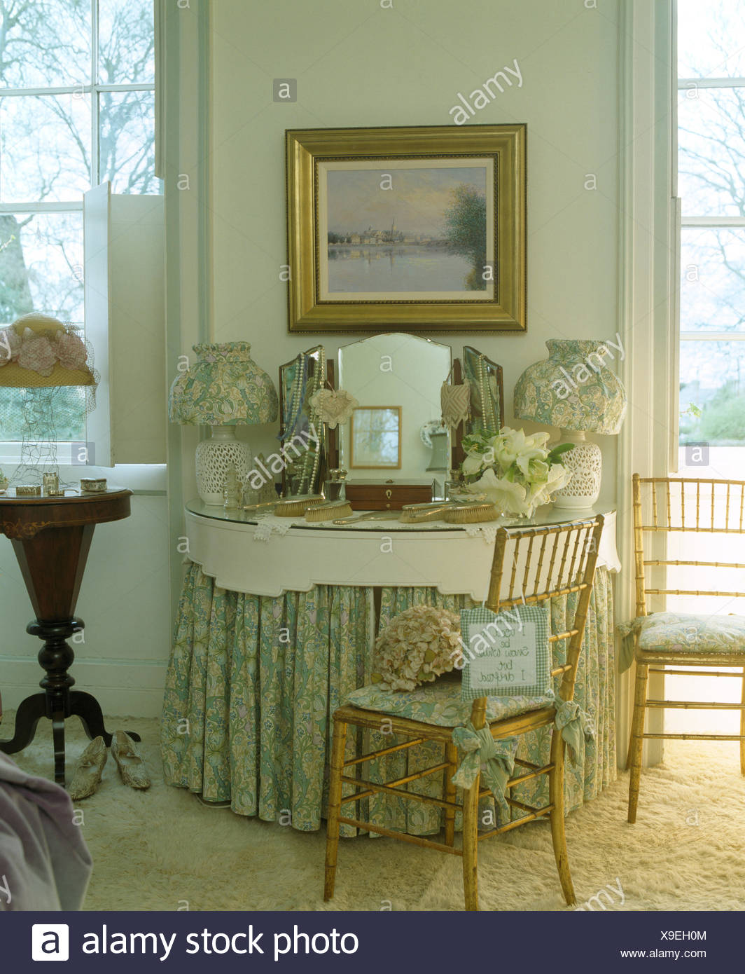 Gilt framed picture above dressing table with green+white drapes in ...