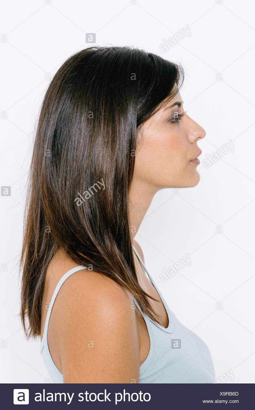 head and shoulder side profile of young woman wearing vest stock