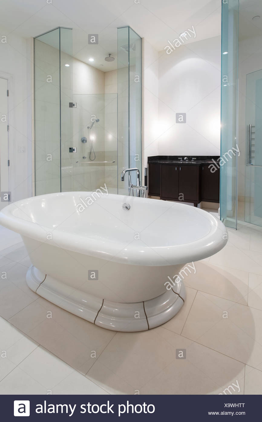 A modern bathroom with a tub floating in the middle of the room and ...