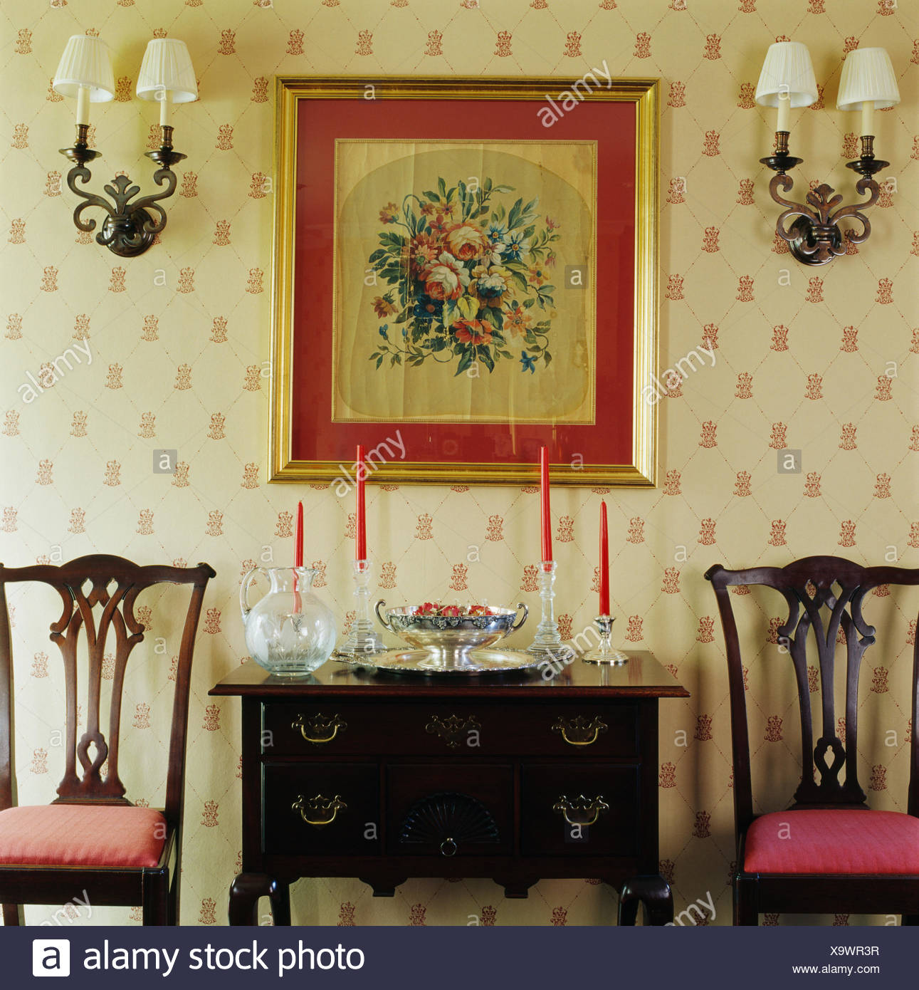 Wall Lights On Either Side Of Framed Floral Tapestry Above Antique Table  And Chairs In Dining Room With Patterned Wallpaper