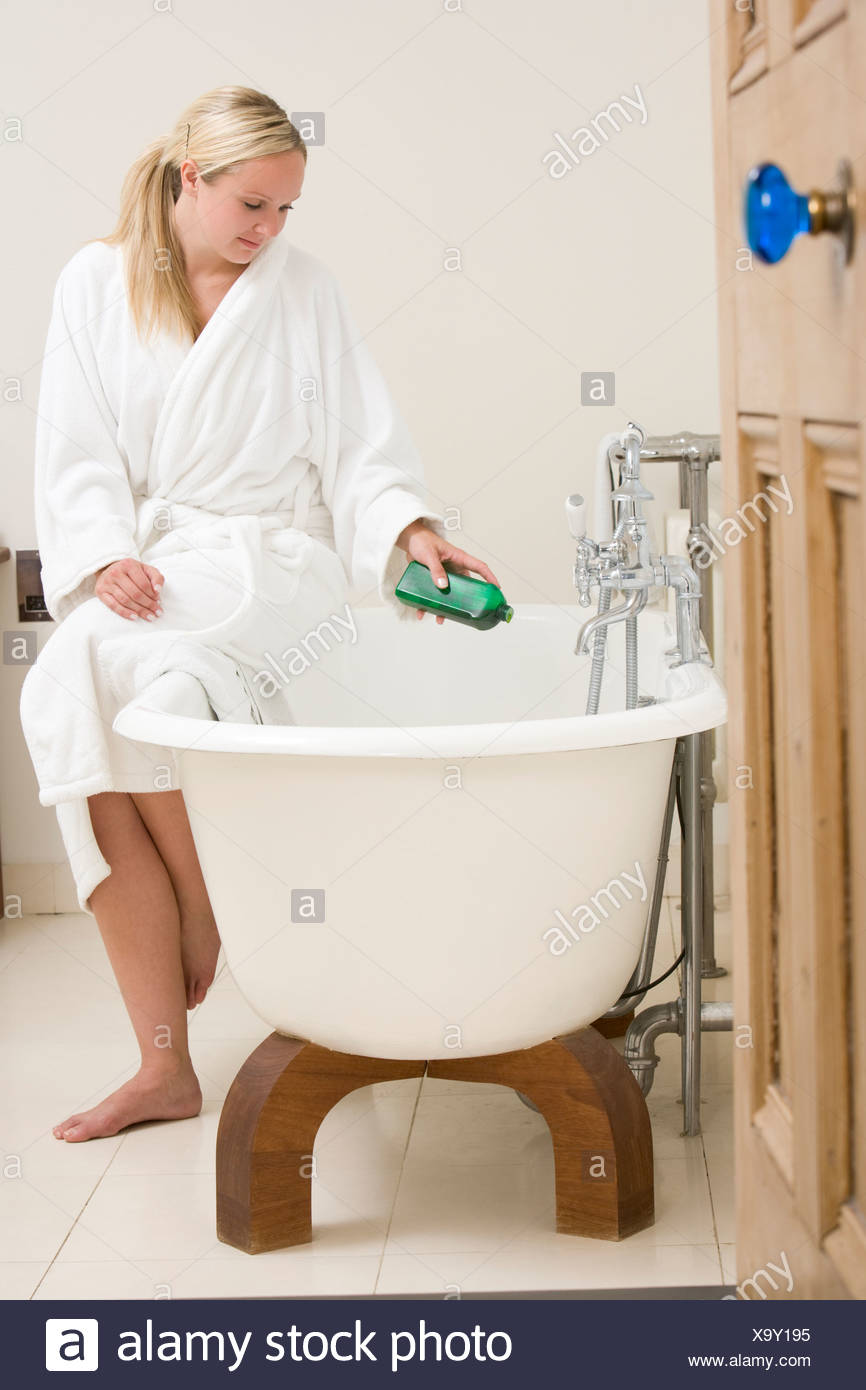 Woman in bathroom putting bubble bath in bathtub Stock Photo ...