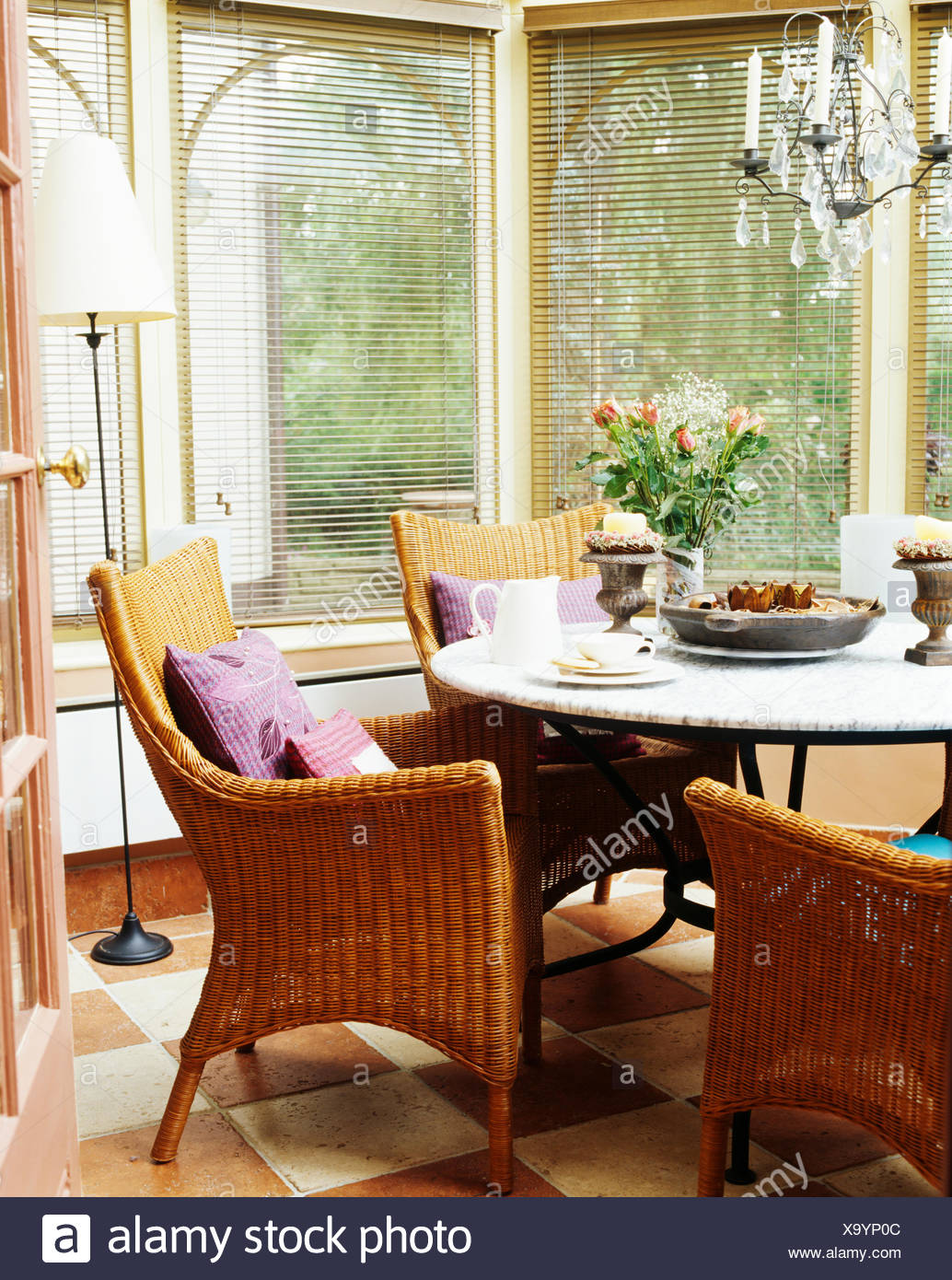 Wicker Armchairs At Circular Table In Conservatory Dining Room With Venetian Blinds On The Windows