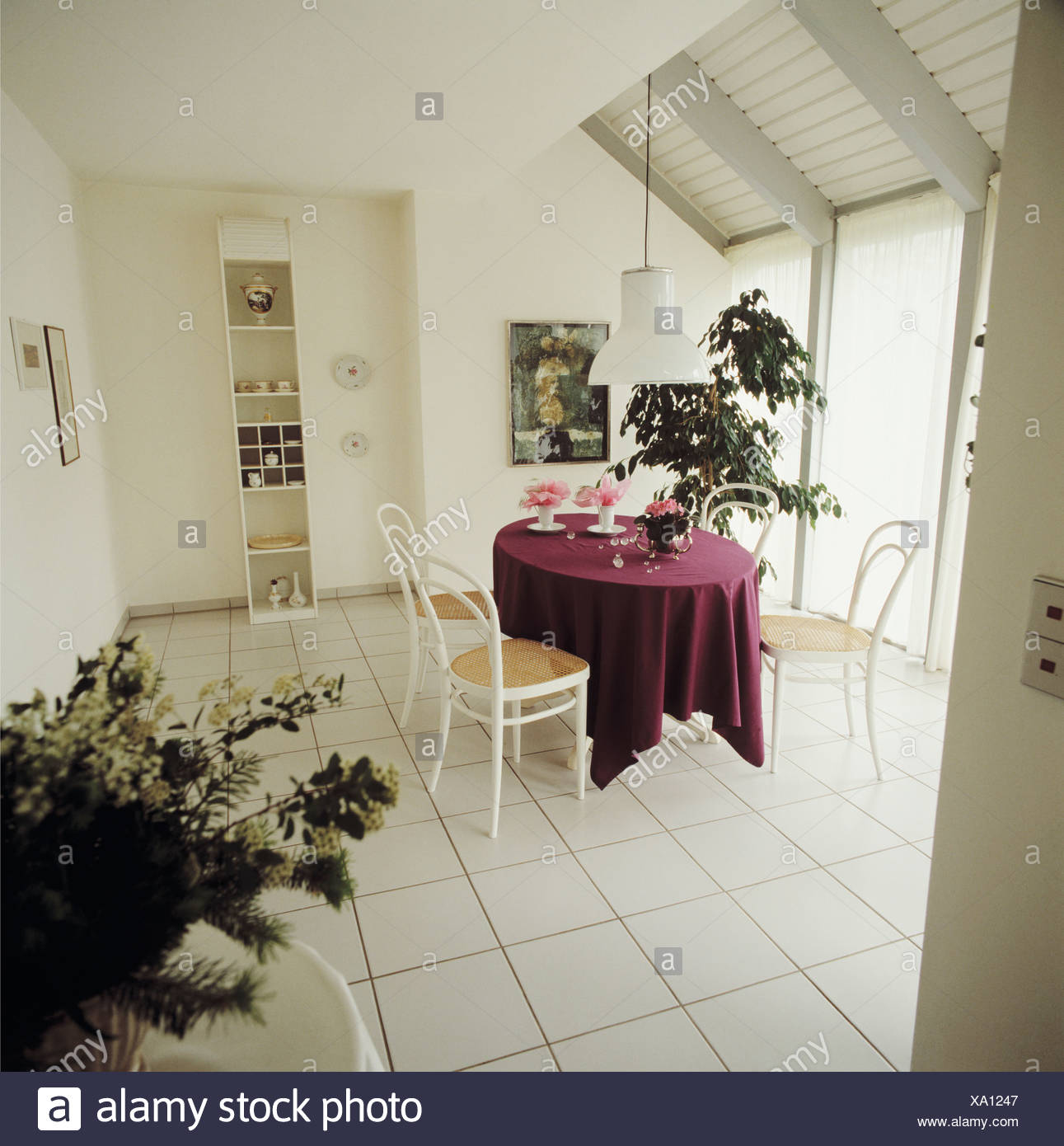 Dark Red Cloth On Oval Table With Bentwood Chairs In White Dining Room With  White Tiled Floor And Green Houseplants