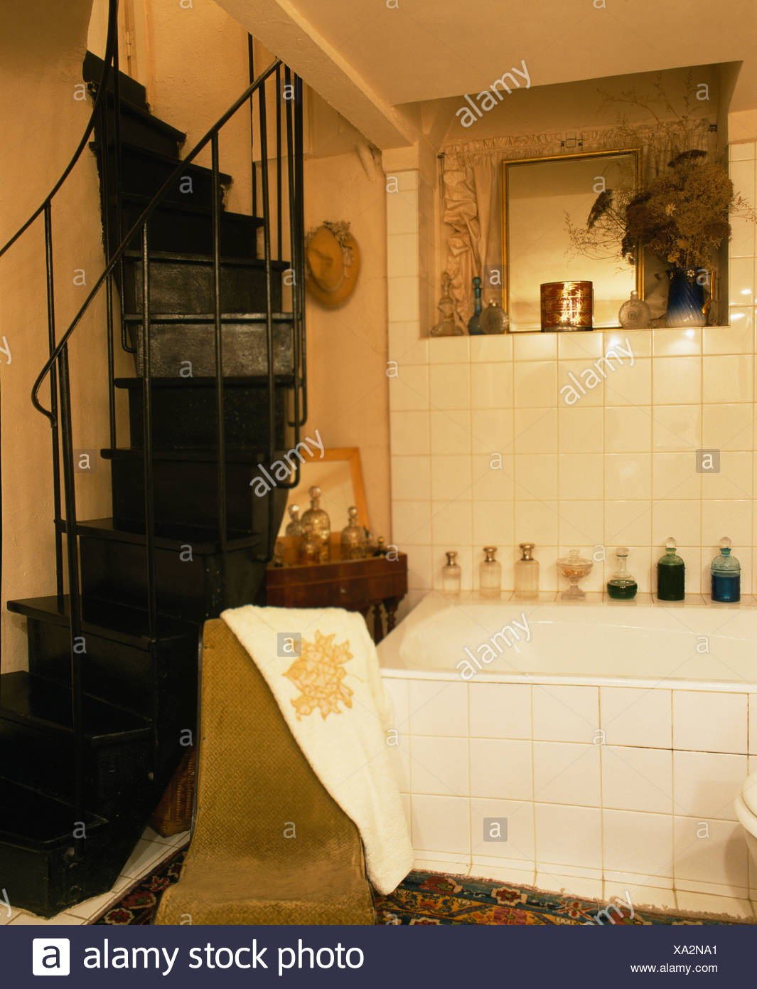 Black spiral staircase in French country bathroom with white tiled ...