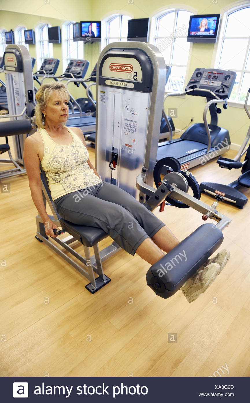 White Woman On Leg Extension Machine In Fitness Center Working