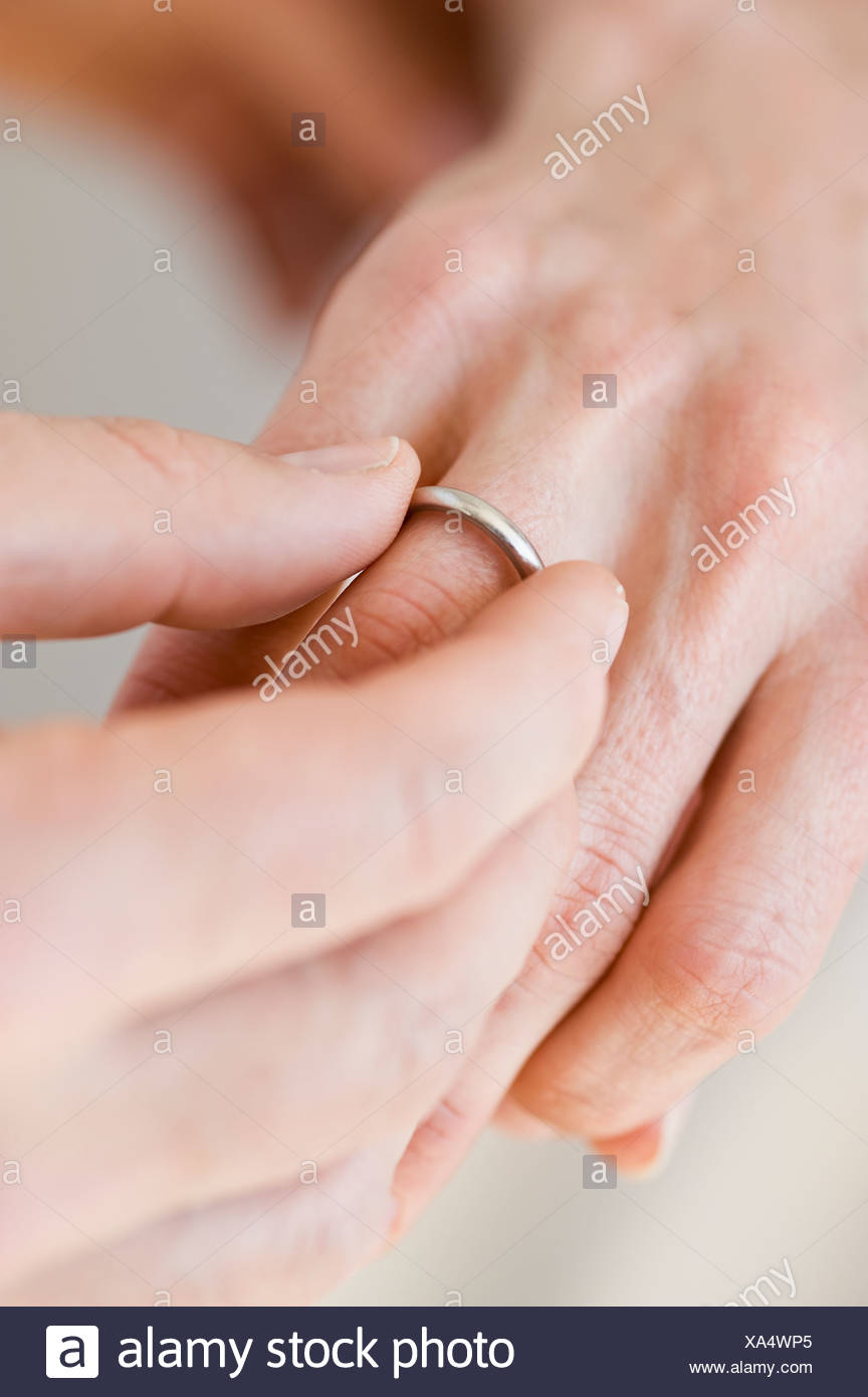 Man putting wedding ring on woman\'s finger Stock Photo: 281620477 ...