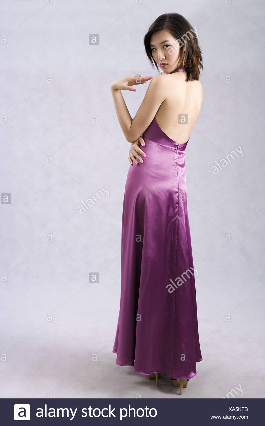 Young woman in purple evening gown rear view head turned Stock Photo ...