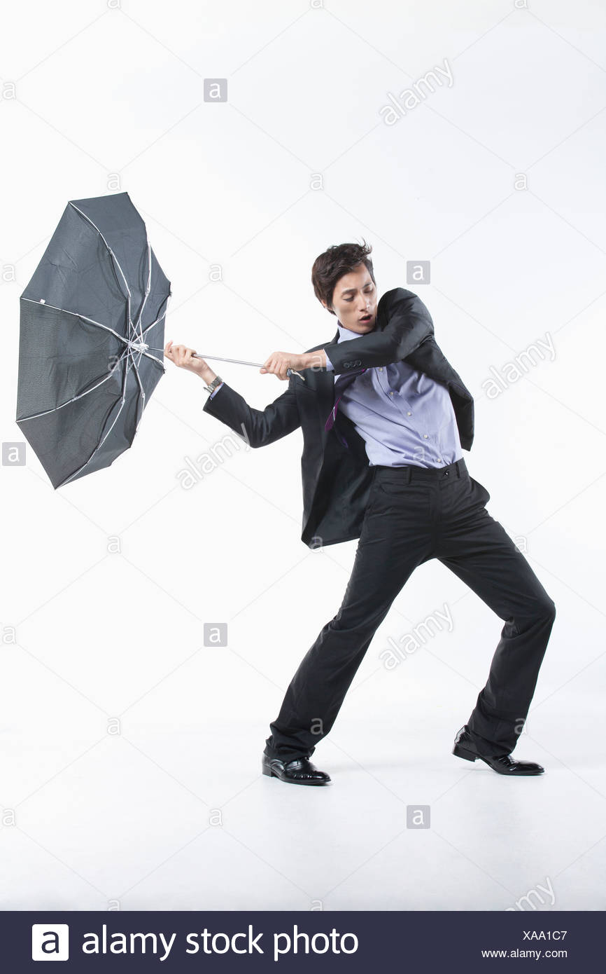 a man hit by the strong wind with an umbrella inside out stock photo