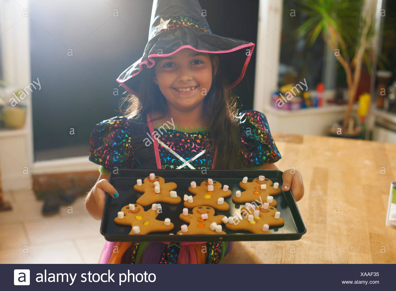 girl wearing halloween witch costume holding tray of gingerbread men