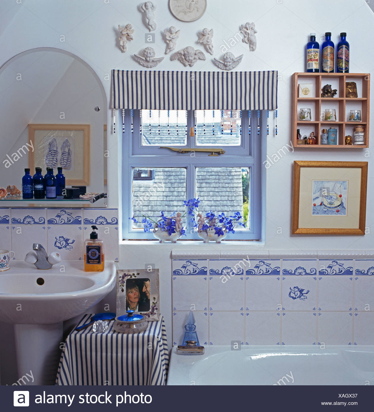 Striped blind on small window in cottage bathroom with blue+white ...