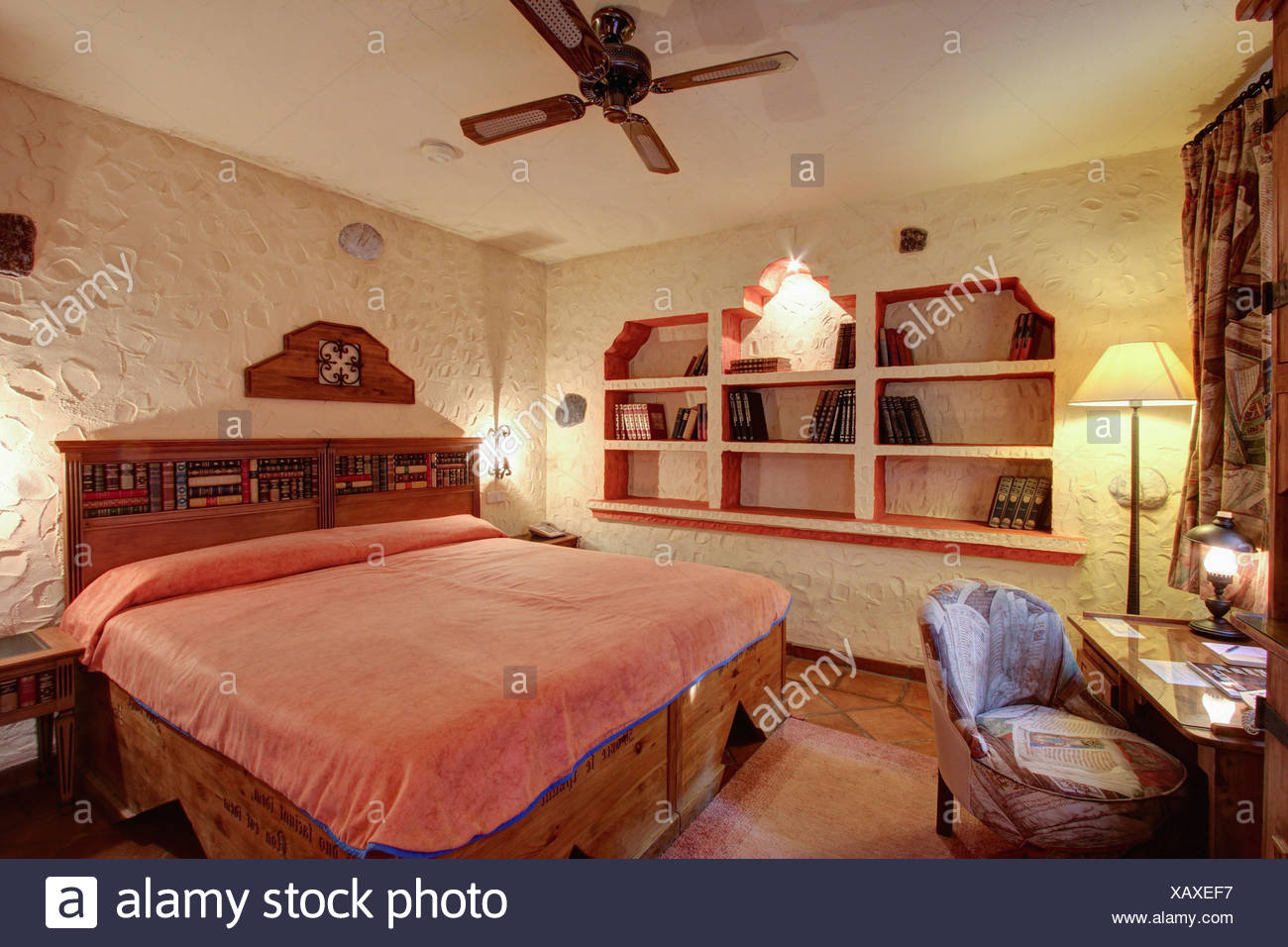 Wooden Bed With Pink Cover In Bedroom With Rough Plaster Walls And Alcove  Shelving In Villa In Southern Spain