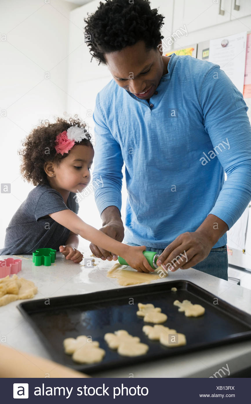 Father and daughter baking sugar cookies in kitchen Stock Photo ...