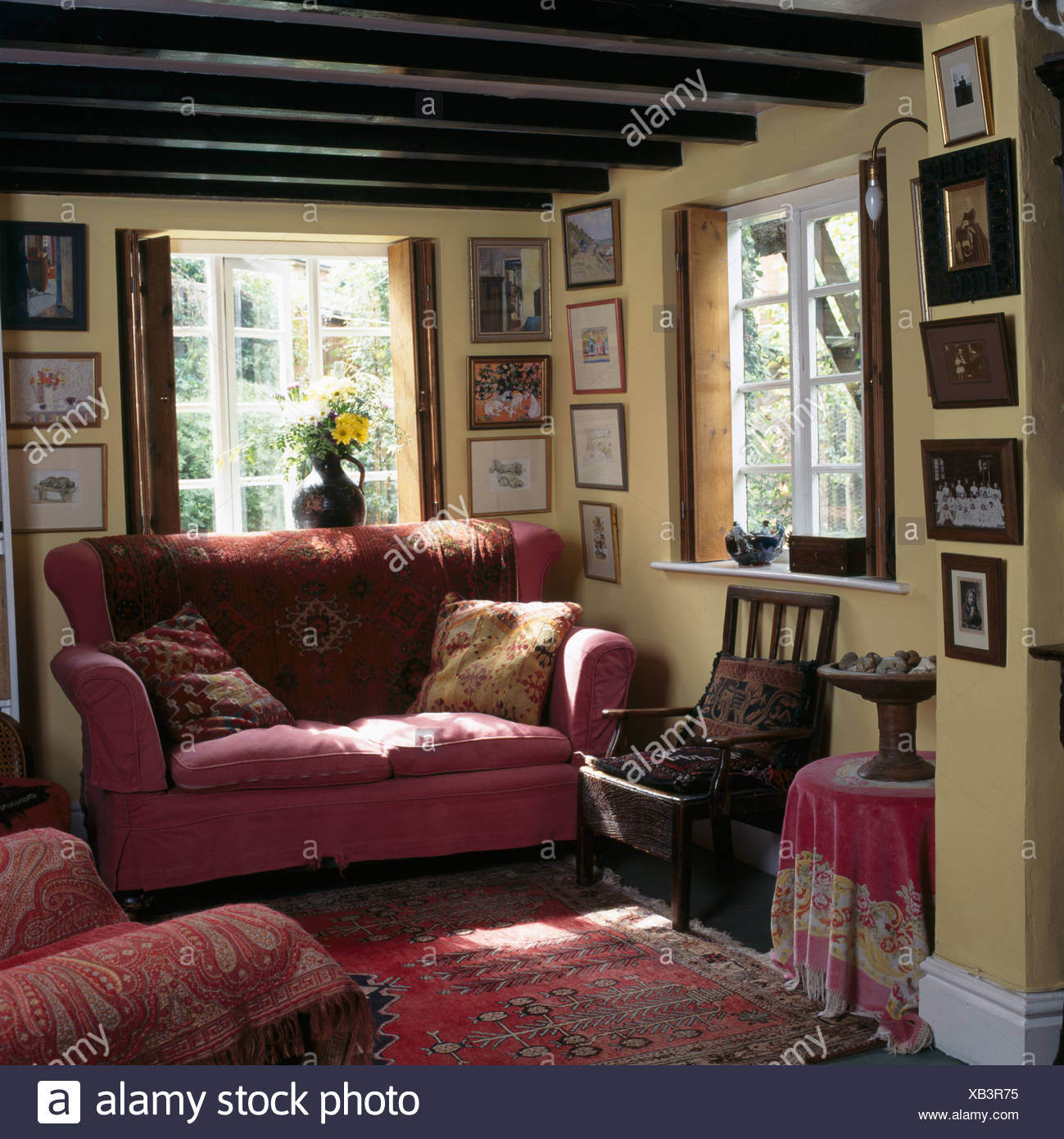 Pink Sofa In Front Of Window In Beamed Cottage Living Room With Collection  Of Small Pictures On The Walls