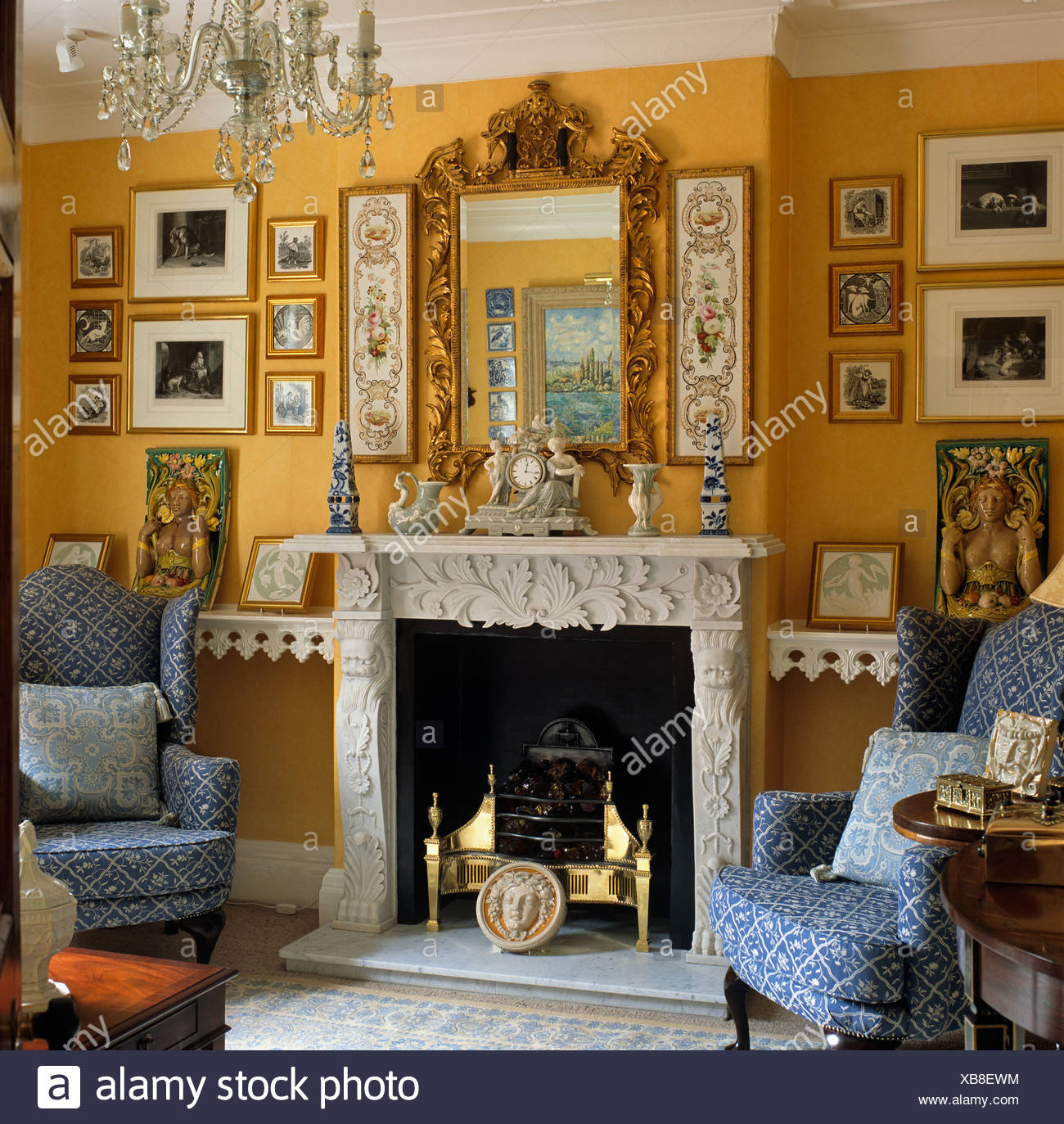 Pictures on either side of antique gilt mirror above ornate fireplace in  pale orange sitting room with blue wing back chairs - Pictures On Either Side Of Antique Gilt Mirror Above Ornate