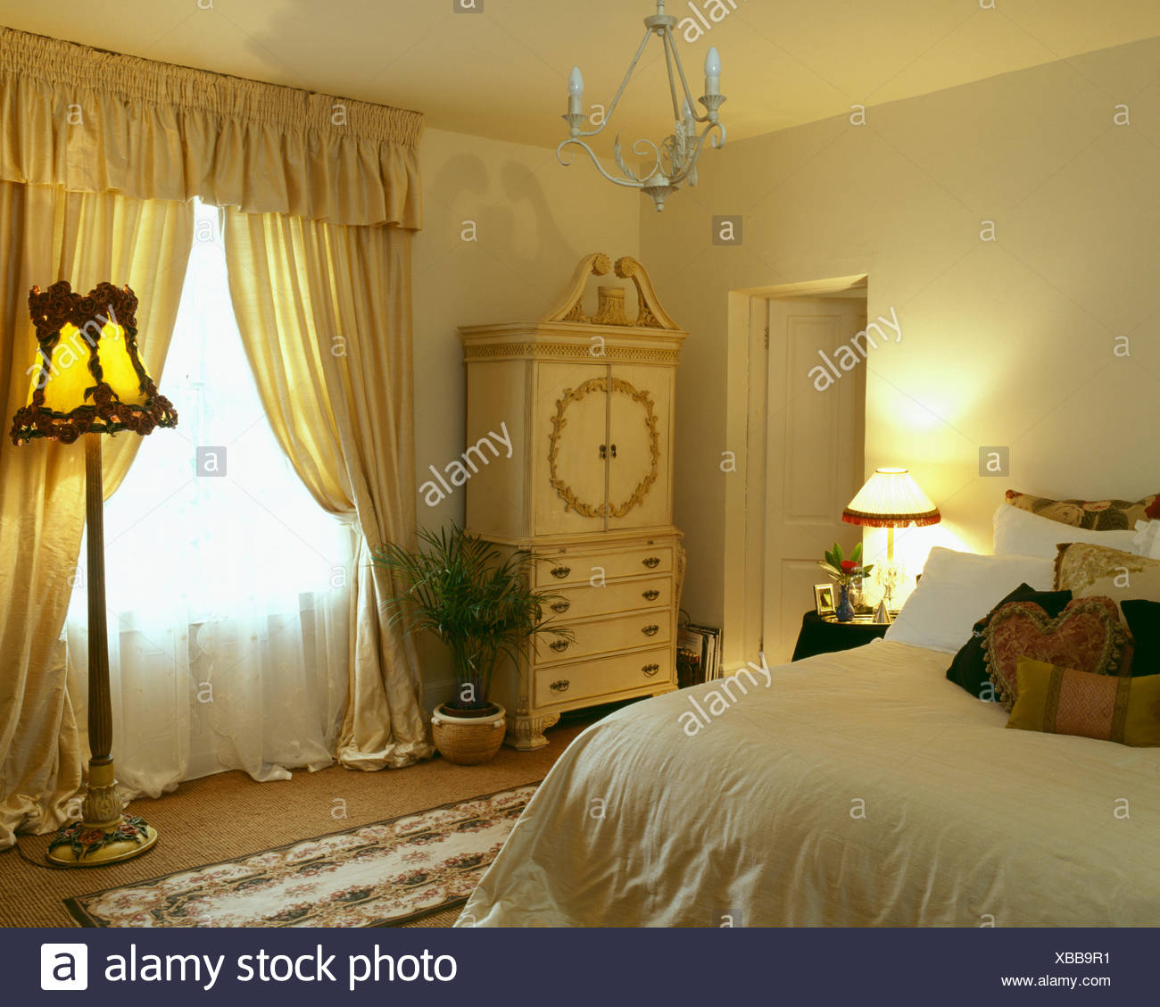 White Voile And Yellow Silk Curtains On Window In Pale Yellow Bedroom With  Lighted Standard Lamp And Cream Cupboard
