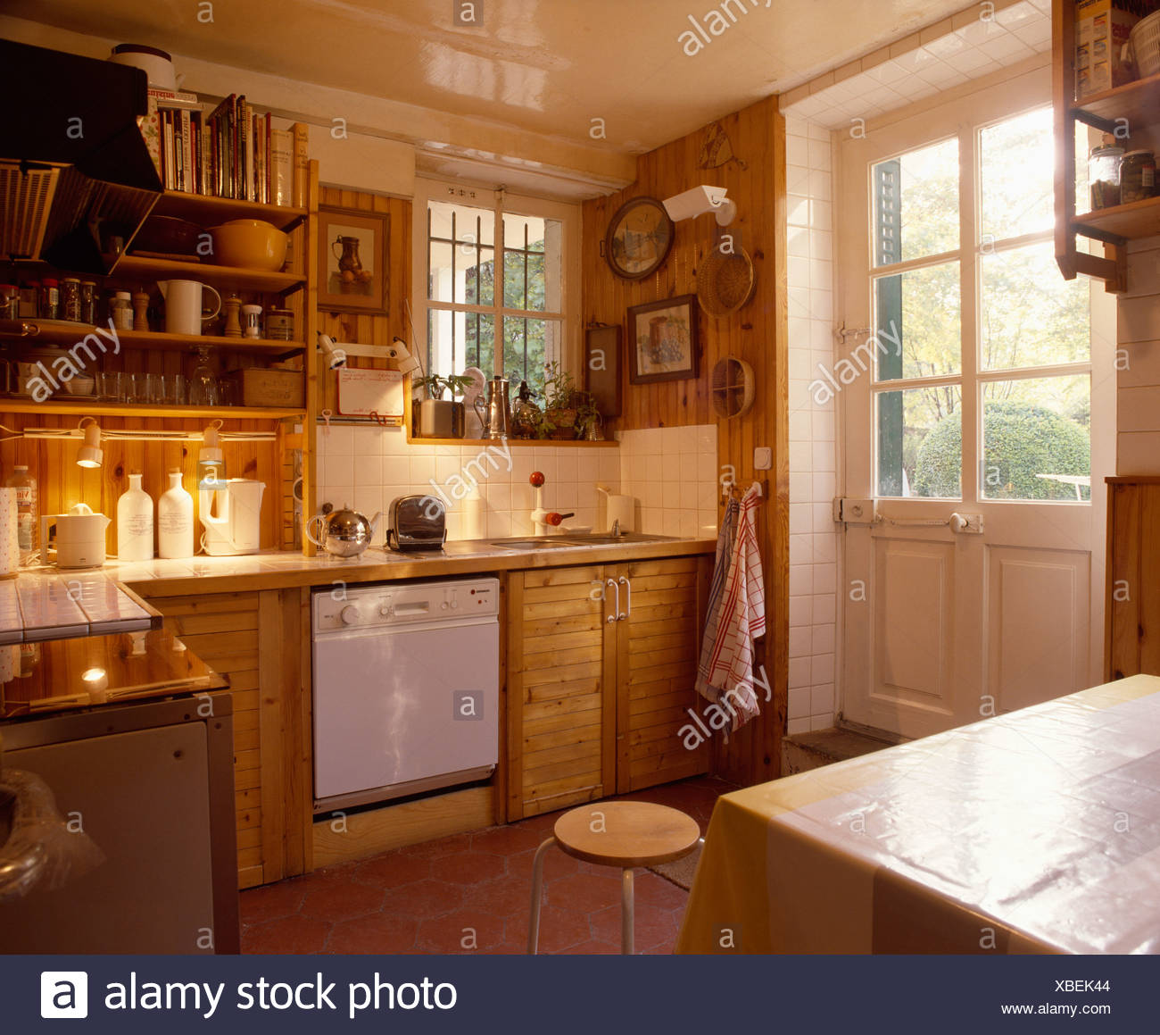 Country kitchen with dishwasher in wooden units below underlit shelves and half-glazed back door : wooden-country-kitchen - designwebi.com