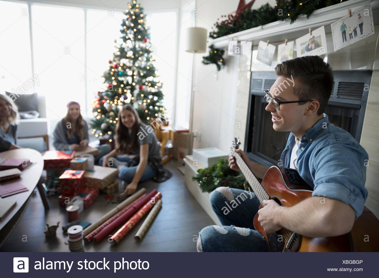 smiling young man playing guitar while sisters wrap christmas gifts in living room with christmas tree