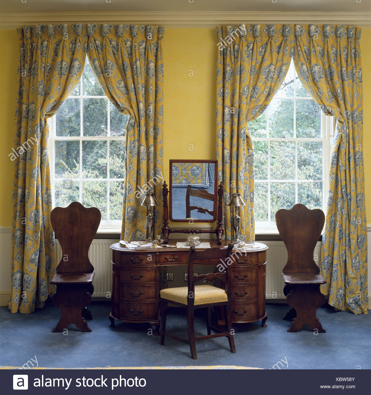 Blue and yellow patterned curtains at windows in bedroom with antique wooden chairs on either side of dressing table