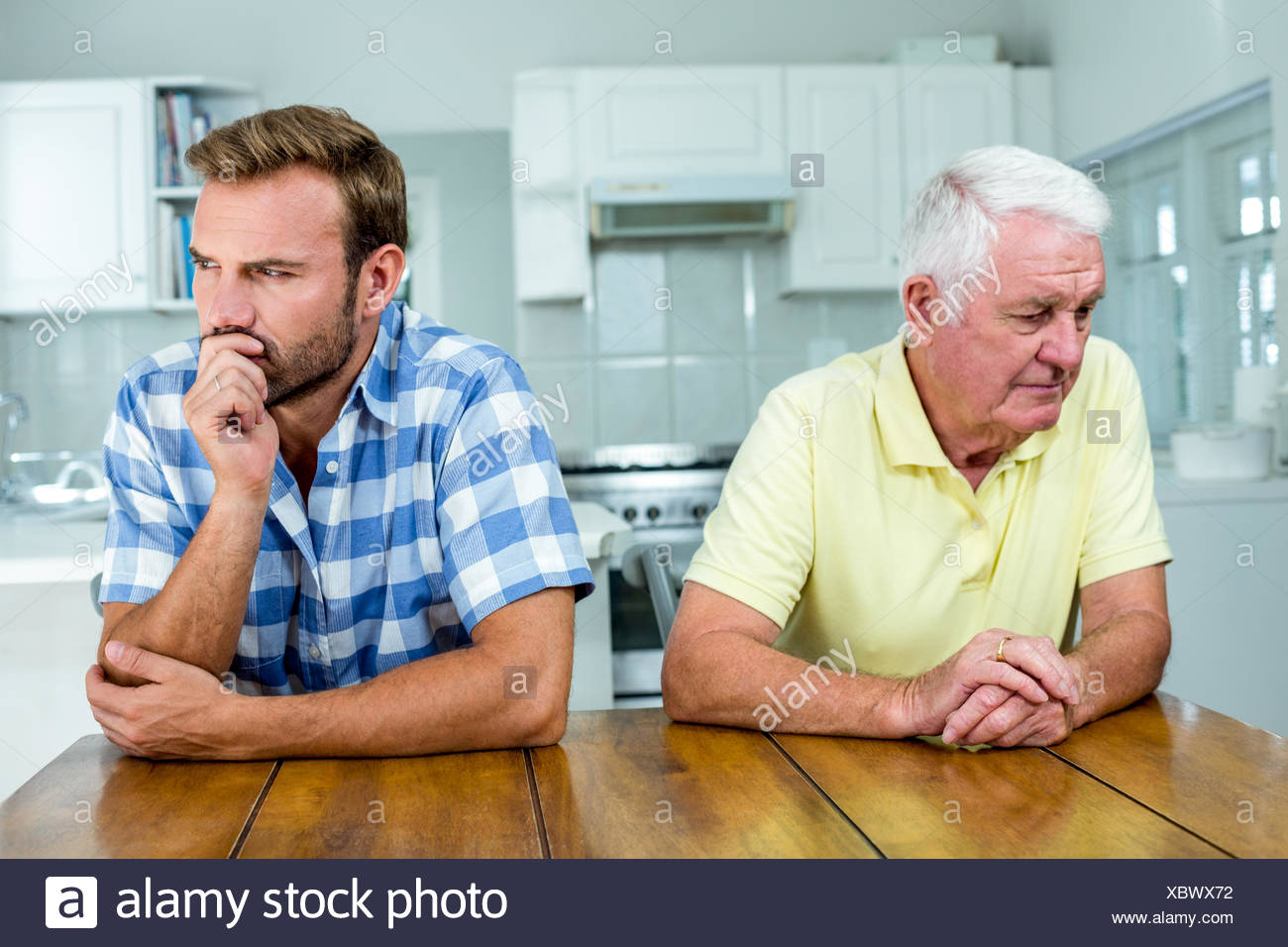 Tensed father and son sitting at table in kitchen Stock Photo ...