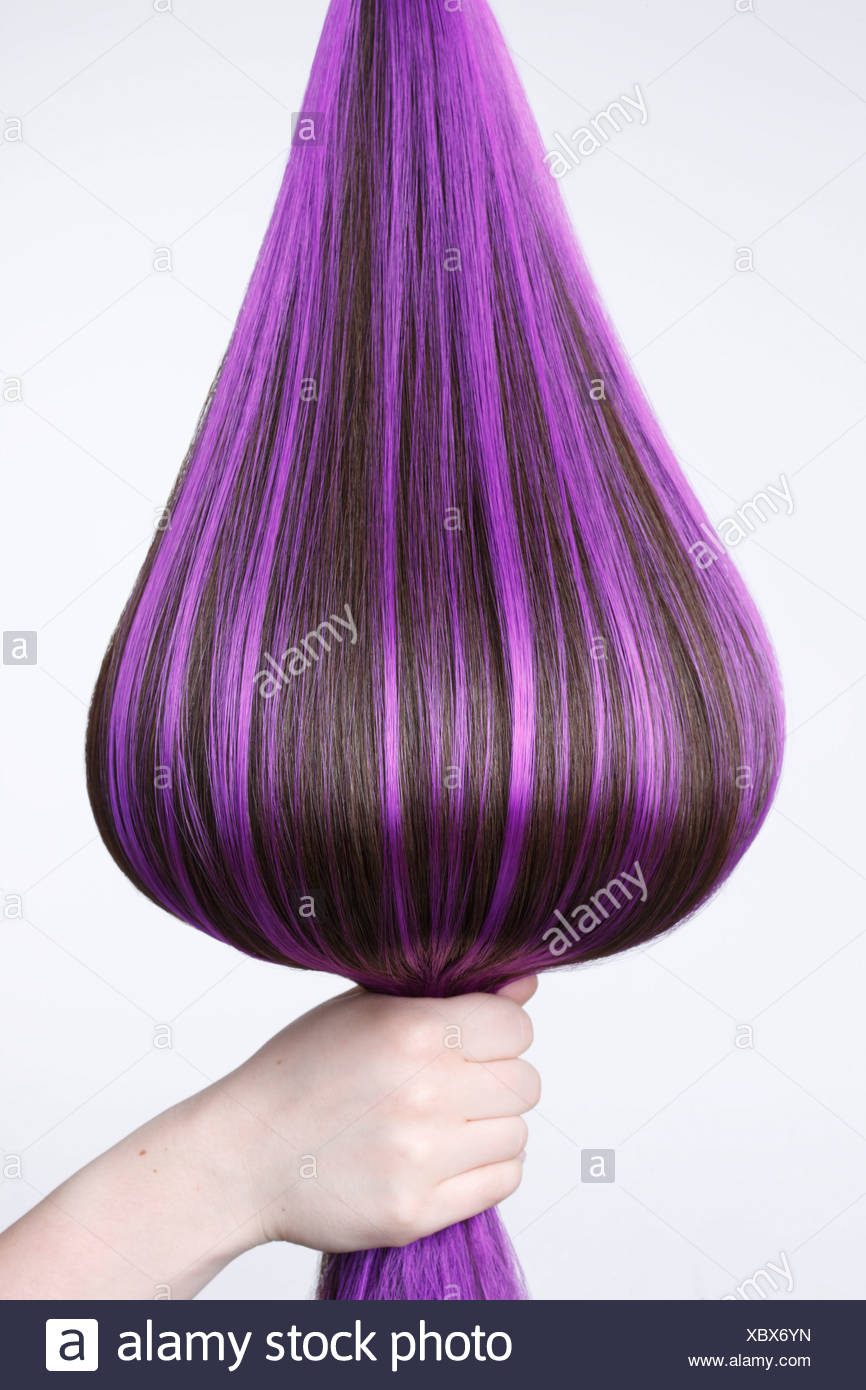Human Hand Holding Brown Hair With Purple Highlights Against White