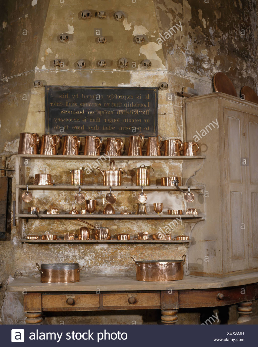 Antique Copper Jugs And Cooking Equipment On Wooden Shelves In Large Old  Kitchen