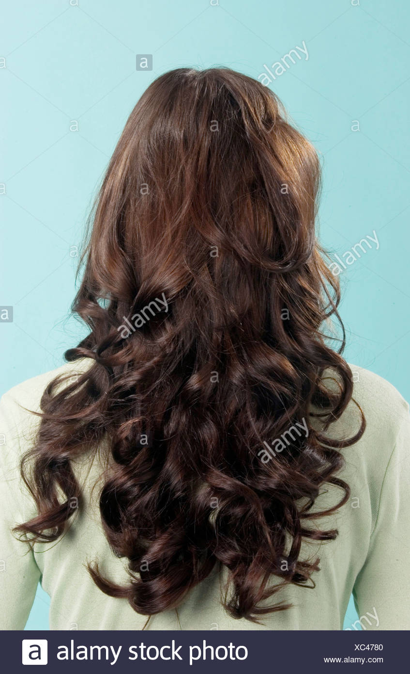 Back View Of Female With Long Curly Brunette Hair Wearing Pale Green