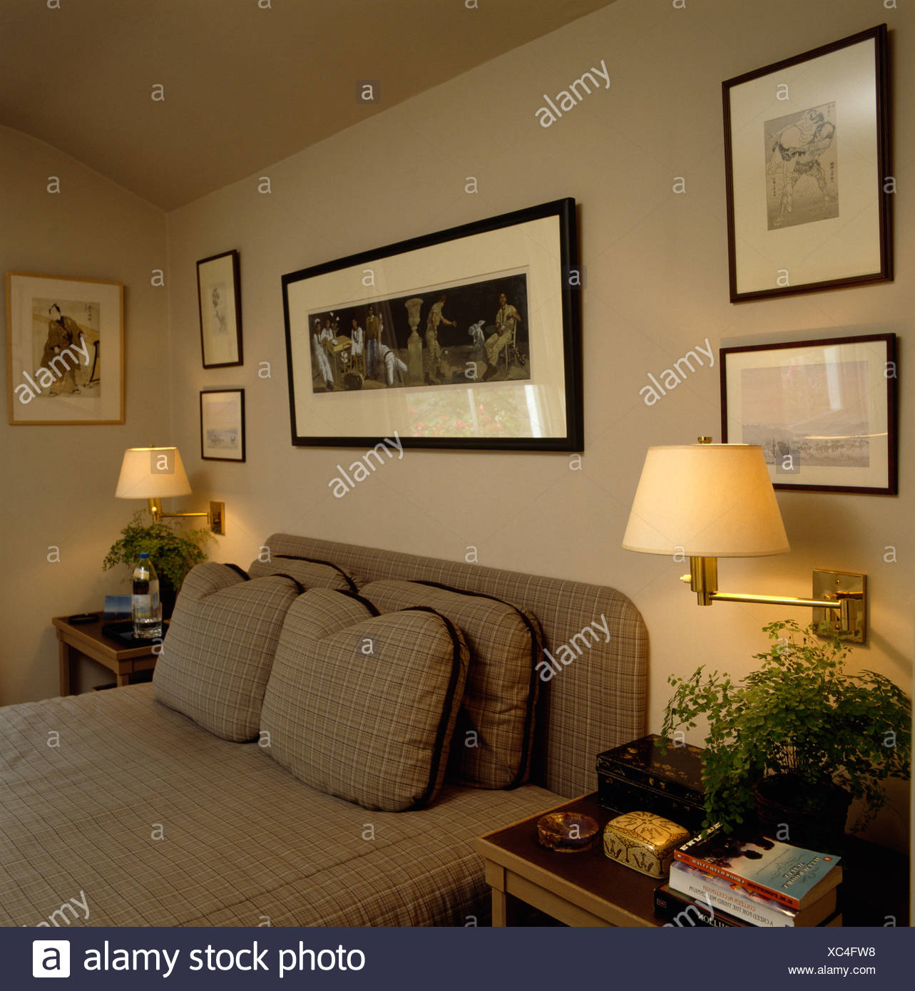 Wall lights on either side of picture above bed with tailed cushions ...