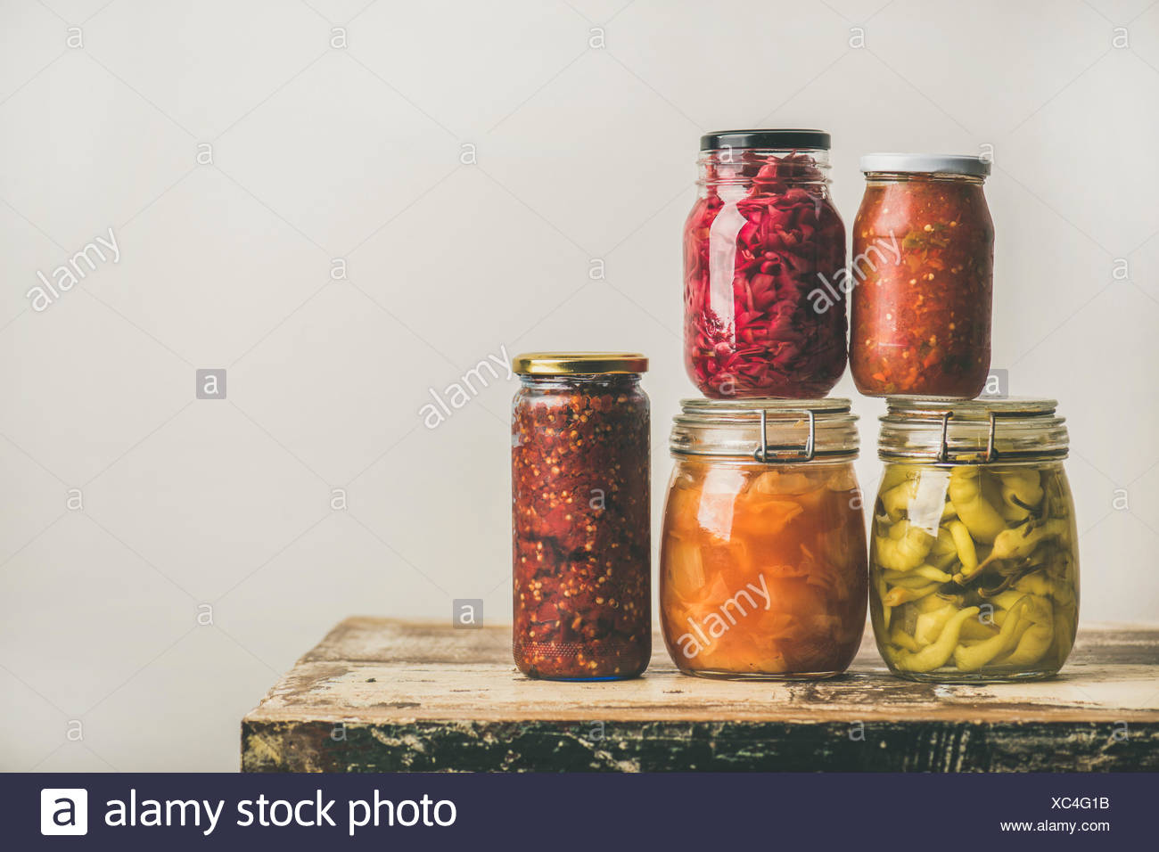 Autumn Seasonal Pickled Or Fermented Colorful Vegetables In Glass Jars  Placed In Stack Over Vintage Kitchen Drawer, White Wall Background, Copy  Space.