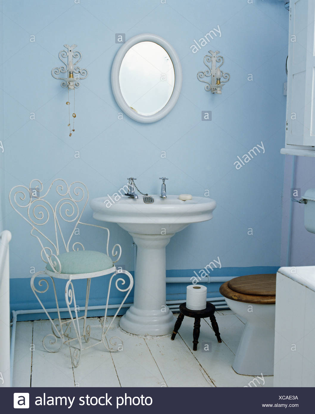 White pedestal basin and metal chair in pale blue bathroom Stock ...