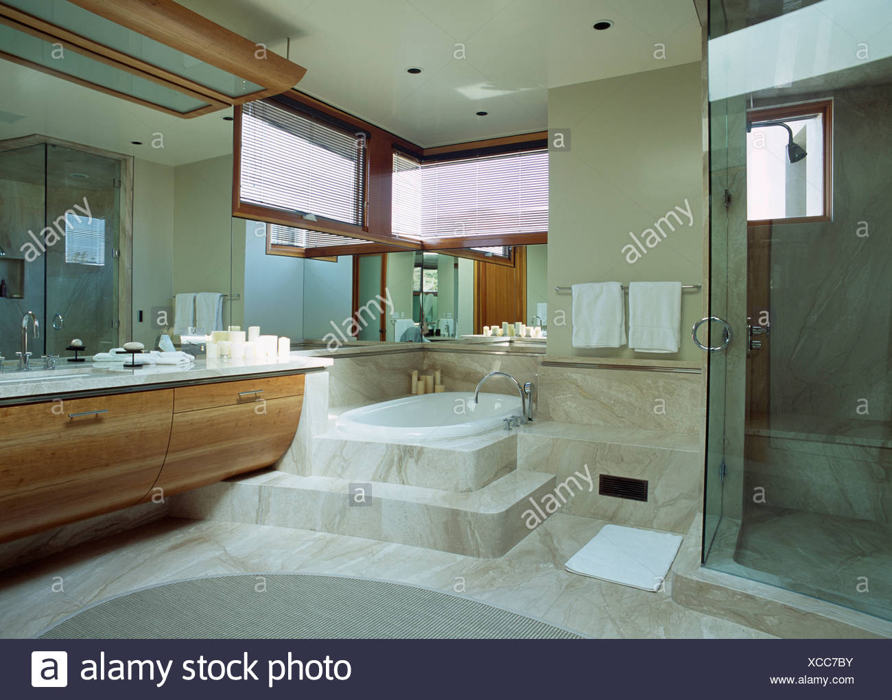 Glass shower cabinet in modern bathroom with marble steps up to bath ...