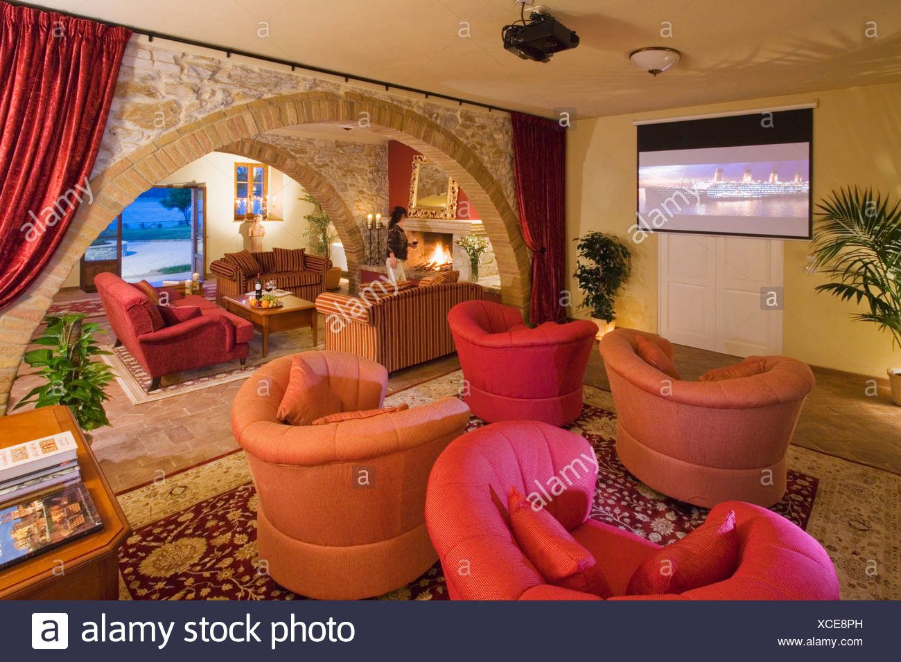 Small cinema screen on wall of Spanish living room with red and ...
