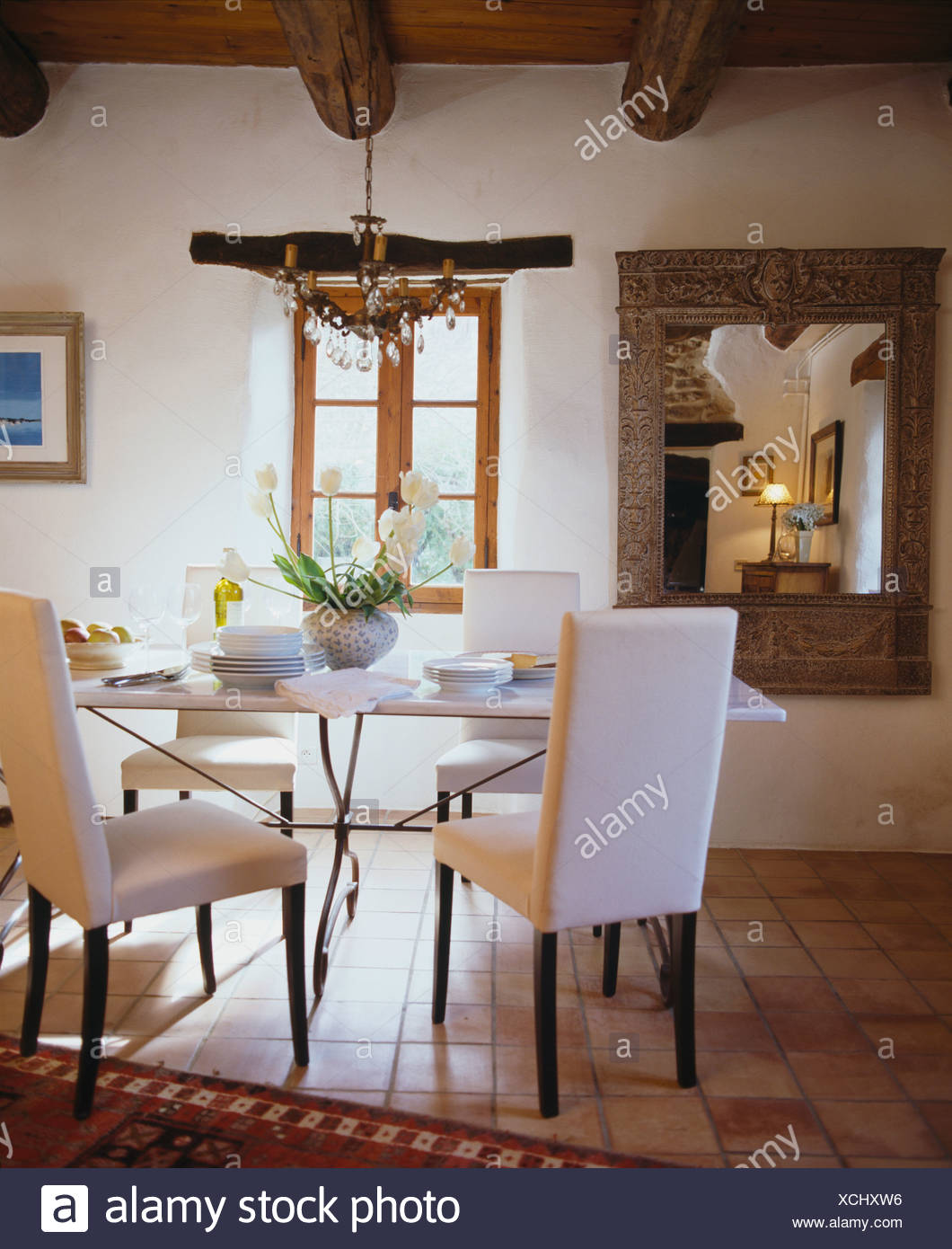 Modern White Upholstered Chairs And White Table In French Country Dining  Room With Large Mirror And Terracotta Tiled Floor