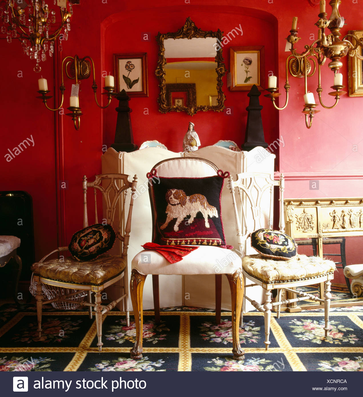 Three Antique Chairs With Tapestry Cushions In Front Of Small White Folding  Screen In Red Living Room With Floral Carpet