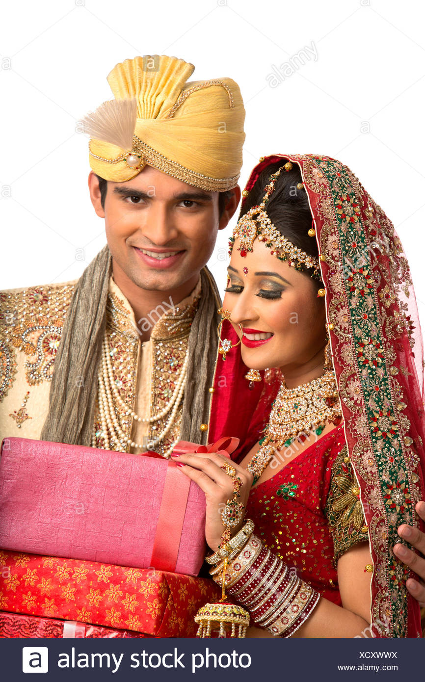 Smiling Indian Newlywed Couple In Traditional Wedding Dress Holding