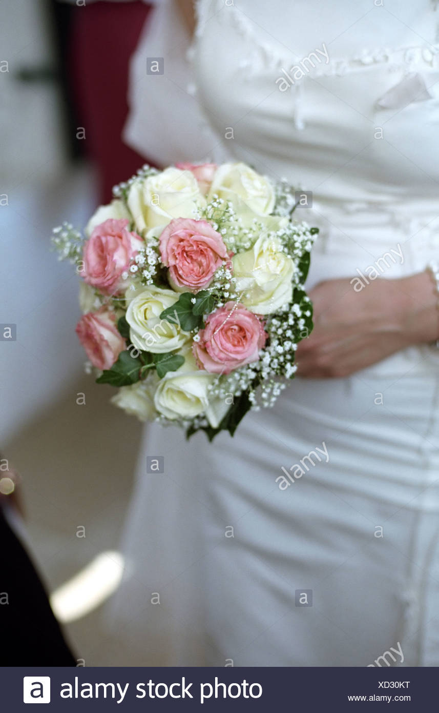 Woman In A Wedding Dress Holding A Bunch Of Flowers In Her Hand