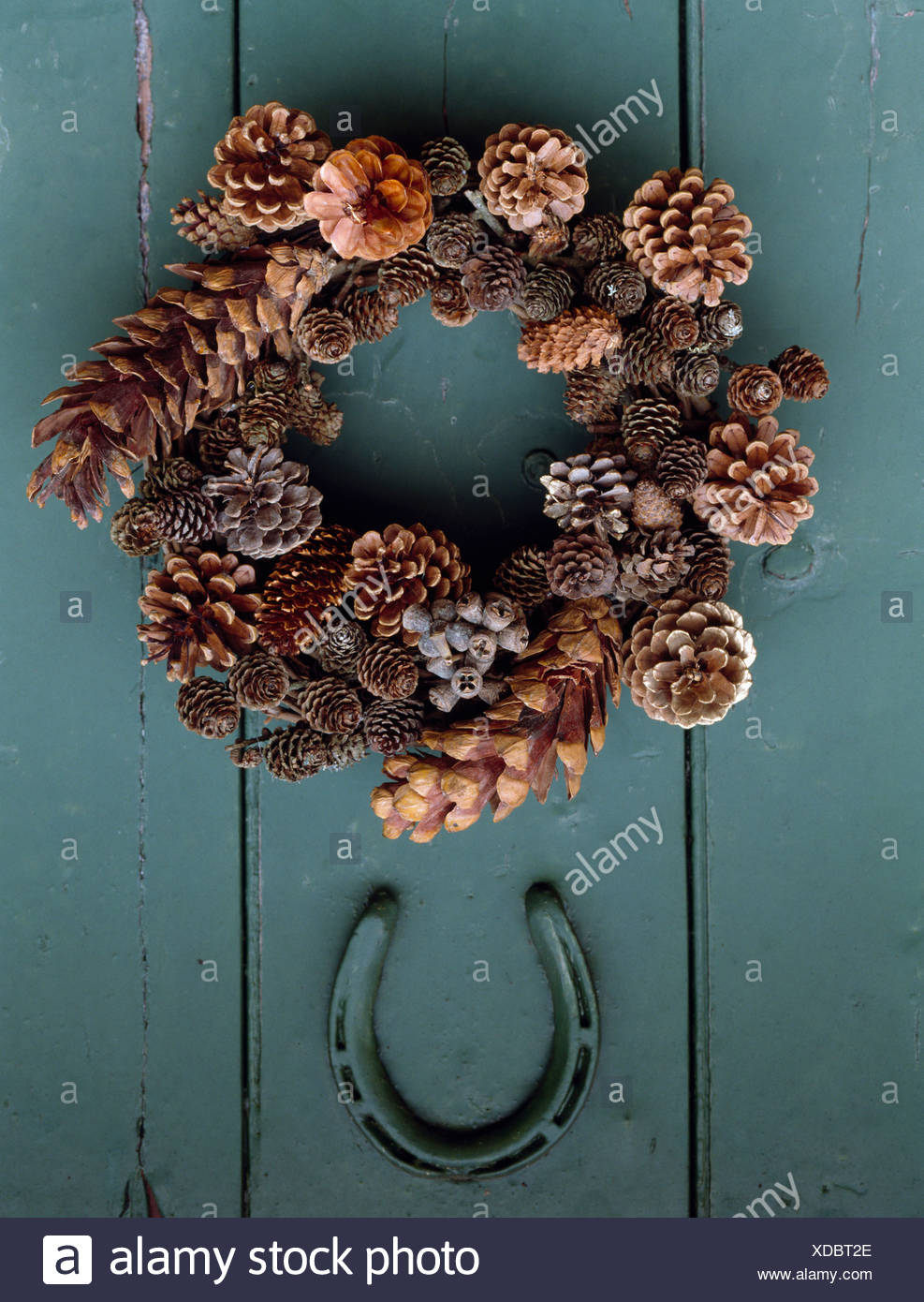 close up of home made pine cone wreath and old horseshoe on grey green painted door - Horseshoe Christmas Wreath